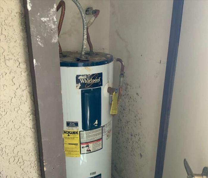 Water heater in a room with concrete floors.