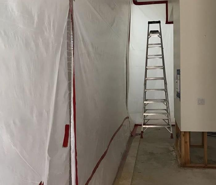 Hallway with plastic wrap on the walls and a ladder at the end.