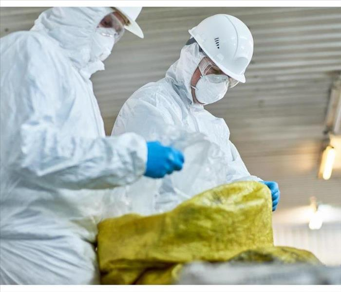 Side view portrait of two workers wearing biohazard suits working at waste processing plant sorting recyclable plastic on con
