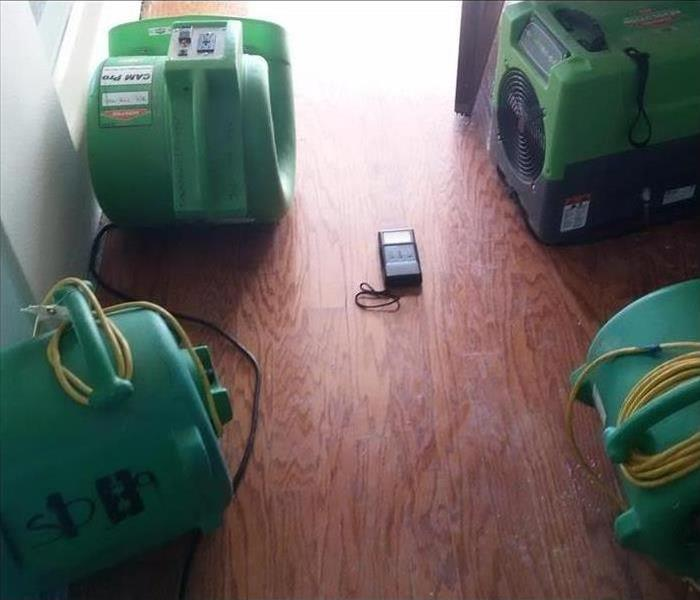 Three air movers a dehumidifier placed on wooden floor. Concept of water damage restoration