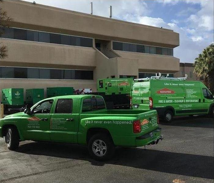 SERVPRO vehicles parked in front of a building to start working on a disaster emergency